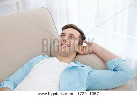 Young man resting on couch with hand behind his head in light room