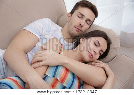 Happy couple resting on couch in light room