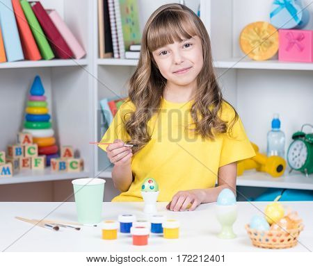 Easter holiday - cute little girl coloring eggs for easter at home. Child having fun and celebrating feast.
