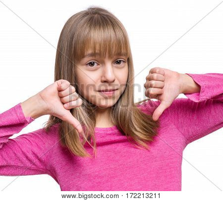Close up emotional portrait of caucasian unhappy girl giving thumbs down hand gesture. Angry child looking with disapproval facial expression, isolated on white background. Negative human face expressions - body language.