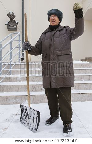 KAZAN, RUSSIA, FEBRUARY 10, 2017. The janitor in winter snow Russian street tell story about politic and salary near museum of Maxim Gorky, portrait