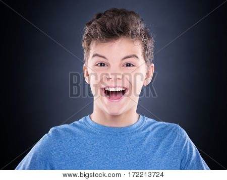 Close-up emotional portrait of caucasian teen boy. Funny teenager wearing blue t-shirt on black background.
