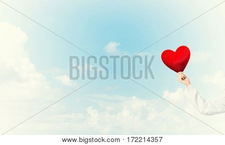 Hand of woman doctor against sky background holding red heart
