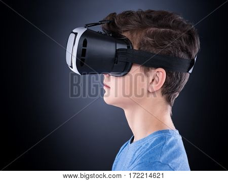 Happy teen boy wearing virtual reality goggles watching movies or playing video games. Cheerful smiling teenager looking in VR glasses. Profile of child experiencing 3D gadget technology - close up.