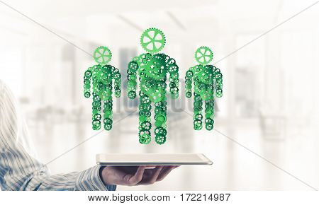Close of businessman holdingn tablet pc with figures of men made of gears. Mixed media