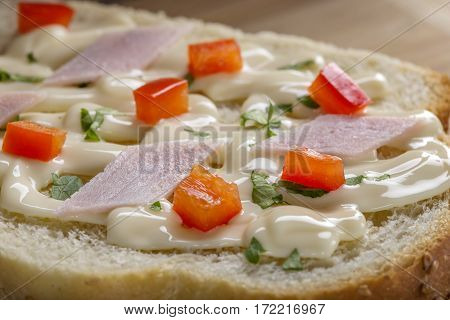 Open sandwich with melted cheese ham and red bell pepper on table