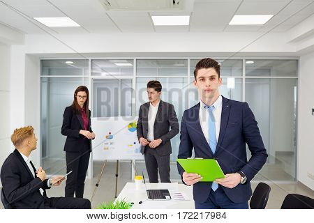 Young businessman working on background of colleagues in the office.