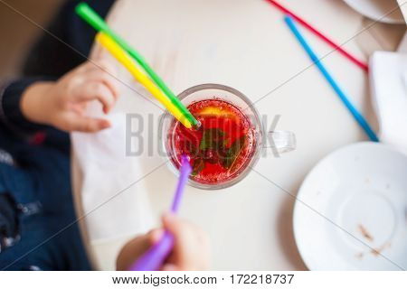 Tea from cowberry and cranberry with mint and lemon in the transparent mug stands on a white wooden table in glass with colored straws.