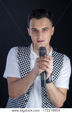 Young Male Black-haired Singer Performs Singing To Microphone