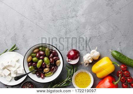 Greek salad main ingredients: fresh olives mix, feta cheese, tomatoes, pepper, cucumbers and olive oil garnished with rosemary on stone background