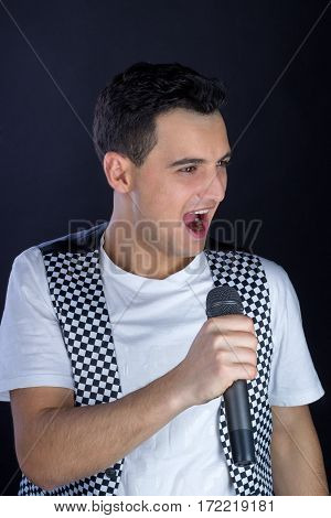 Young Male Black-haired Pop Singer Singing To Microphone