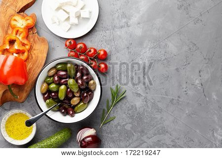 Greek salad basic ingredients: fresh olives, feta cheese, tomatoes, pepper, cucumbers and olive oil on stone background