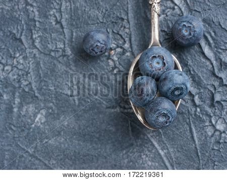 Freshly picked blueberries in spoon closeup. Ripe and juicy fresh blueberry on textured concrete background. Bilberry on dark background with copyspace. Blueberry antioxidant. Top view or flat lay