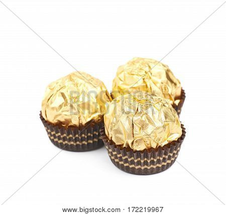 Pile of golden confection candies isolated over the white background