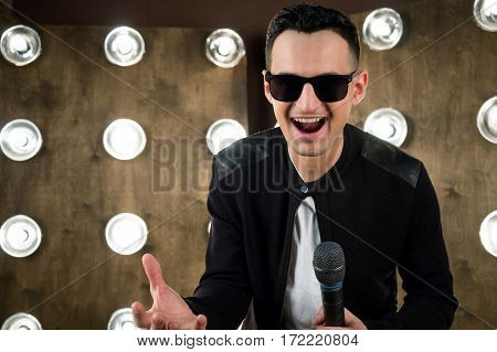 Male Singer In Sunglasses Performing On Scene In Projectors Lights
