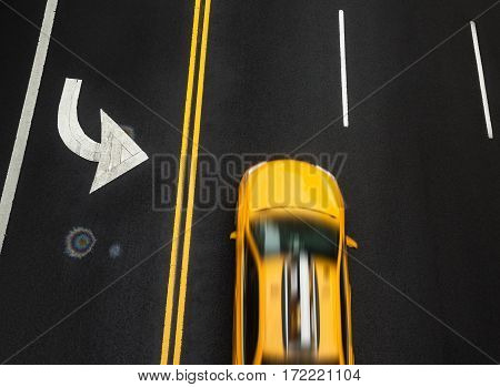 Road markings on asphalt on the street of Manhattan in New York City. Motion blured taxi cab moves along the road with a high speed. Iridescent spot of gasoline on asphalt