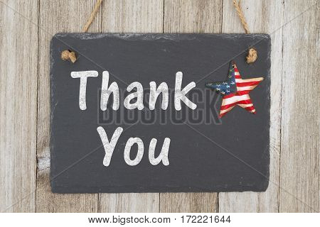 A rustic patriotic thank you message A retro chalkboard with a vintage USA star hanging on weathered wood background with text Thank You
