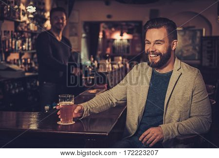 Stylish man sitting alone at bar counter with a pint of beer