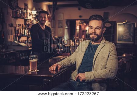 Stylish man sitting alone at bar counter with a pint of light beer