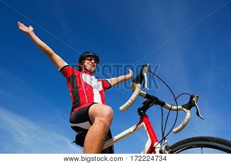 Cyclist raising his arms, crossing the finish line acros a deep blue sky, seen from below