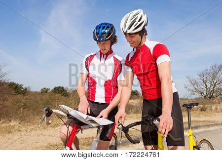 Two cyclists looking at a map for directions, stading over their bicycles