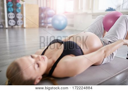 Pregnant Woman Training With Pilates Ball Between Legs