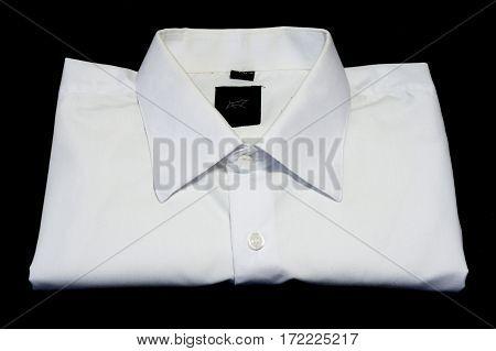 Folded smoothed elegant white shirt on black background. Man`s fashion. In shirt sleeves.