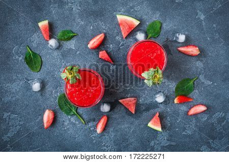 Watermelon juice. Summer cocktail with watermelon and strawberry on stone background. Top view flat lay