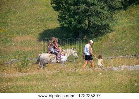 PLUZINE, MONTENEGRO - JULY 27, 2016: a family are strolling on summer countryside: mother and two daughters on the horse, father and daughter on foot