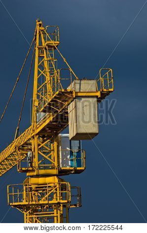 Yellow construction crane against dark blue sky in Belgrade, Serbia