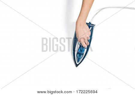 Female hand ironing clothes top view isolated on white background. Young woman seen from above during housework. Blue iron on white table.