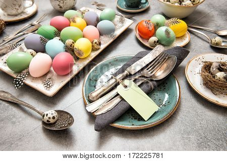 Easter still life. Festive table place setting decoration with colored eggs