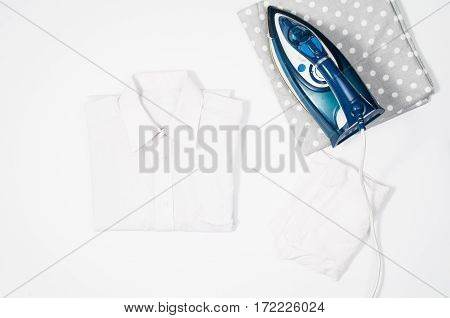Female hand ironing clothes top view isolated on white background. Young woman with iron ironing man's shirt seen from above during housework. Blue iron on white table.