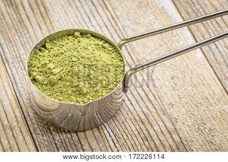 matcha green tea powder in a metal measuring scoop against grunge wood background