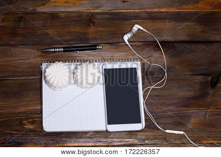 Mobile Phone With Pad And White Headphones, Marshmallows And Pen