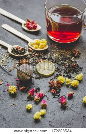 Teacup and herbs on dark grey stone background