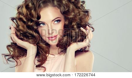 Beautiful girl with long wavy  and volume  shiny  hair . Brunette woman  with curly hairstyle