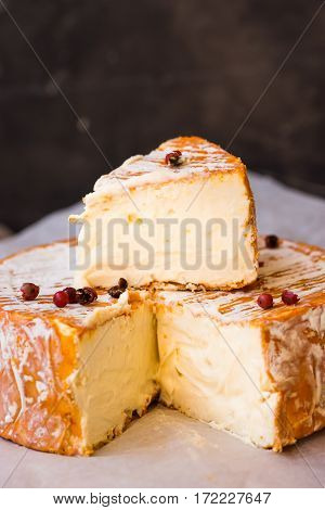Soft cheese with cut off slice creamy texture orange rind with mold French German Alps red pepper corns close up