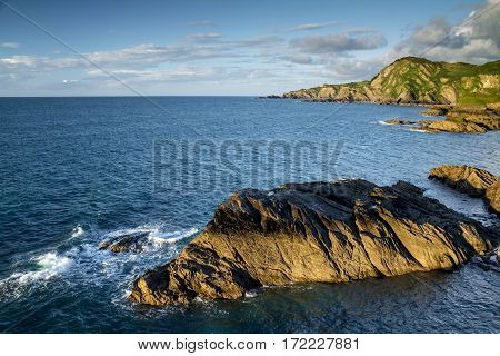Colorful seascape with rocky coastline. The low evening sun. In the foreground is part of the rock. North Devon. UK