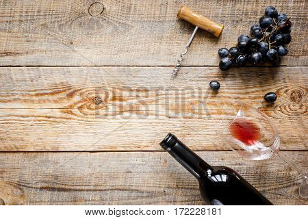 Glass of red wine and bottle with grape on wooden table background top view mock-up