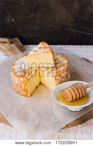 Soft cheese with cut off slice creamy texture orange rind with mold French German Alps honey dipper top view rustic kitchen interior