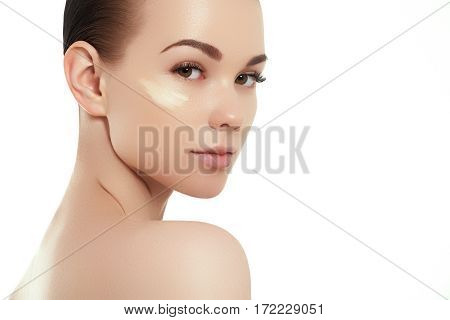 Beautiful Girl Applying Some Cream To Her Face. Youth And Skin Care Concept. Woman Beauty Face Portr