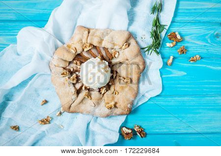 homemade cake with pears and ice creams on blue wood background.