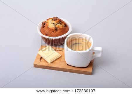 Classic espresso in white cup with cake and chocolate on white background