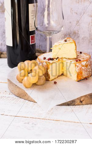 Soft cheese with cut off slice creamy texture orange rind with mold, red pepper corns, grapes, wine bottle and glass rustic kitchen interior