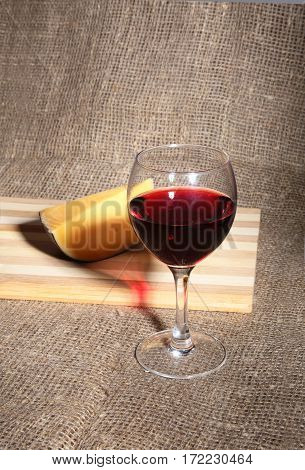 Glass with red wine grapes and chees on wooden table
