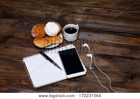 White Cup Of Coffee With Headphones And Mobile Phone, And Lying Next To Notebook With Pen, Croissant