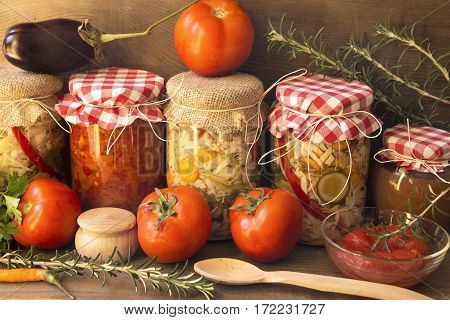 Pickled and fresh vegetables with spices on wooden shelf