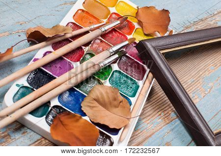 Paints, brushes for painting and frame with dry leaves