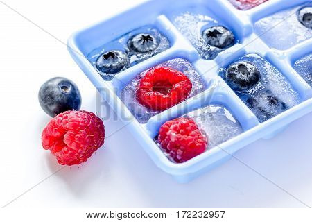 Icecubes with blue icetray and blueberries and raspberries on white table background